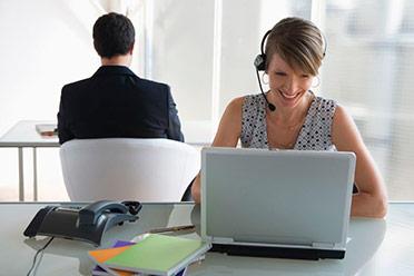 23891114-mujer-de-negocios-con-kit-manos-libres-de-trabajo-en-la-computadora-portatil-colega-masculino-en-el-